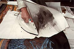 Ironing out the wax with newsprint paper between iron and cotton.